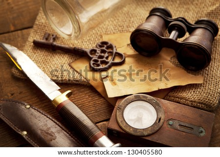 Treasure hunting setting, A compass, binoculars, knife and a old key on a old wooden desk - stock photo
