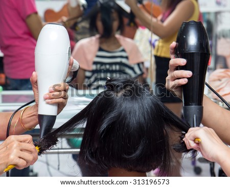 Treatment of hair in a hairdressing salon. Hair stylist modeling hairstyle woman using a hairdryer. Professional team for hair care.