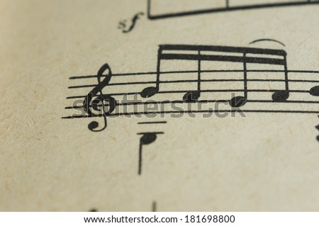 Treble clef and some notes close up on the page - stock photo