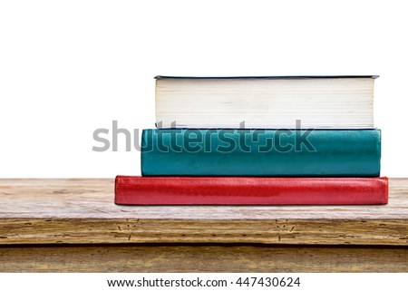 tree aged book stack on wooden table isolated on white background.