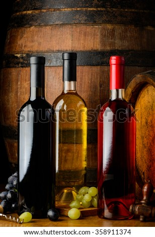 Tree bottles of wine in a vintage wine cellar. Red, white and rose wine on wooden background - stock photo