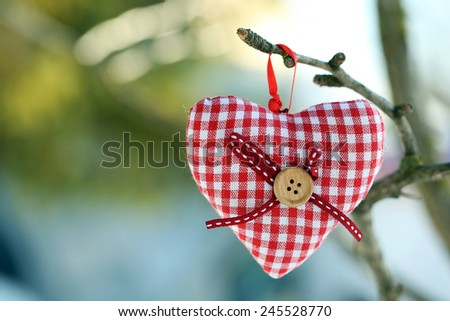 Tree branch with heart decoration on nature background - stock photo