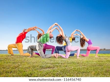Tree couple , man and woman practice Yoga asana on lakeside. Yoga concept. - stock photo