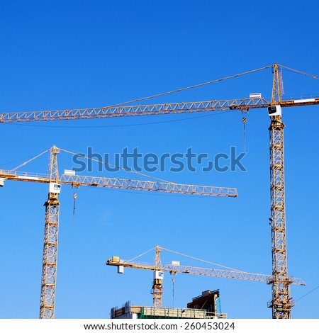 Tree cranes and building construction on blue sky background, square image  - stock photo