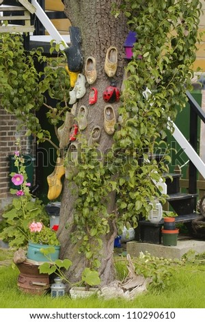 Tree, decorated with lots of wooden clogs - stock photo