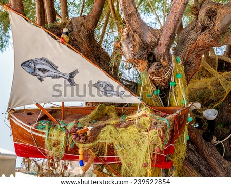 Tree, decorated with old red fishing boat. - stock photo