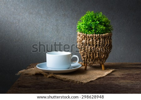 Tree decorative with cup of coffee on wooden table over wall grunge background - stock photo
