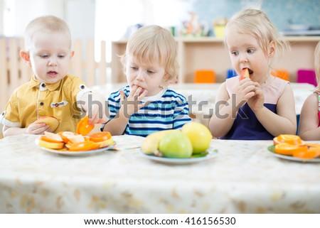 Tree funny kids eating fruits in day care centre - stock photo