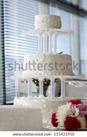 tree  level white wedding cake on table with flowers - stock photo