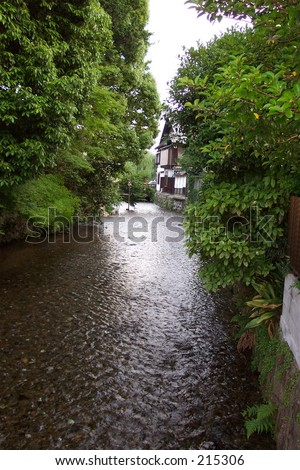 Tree lined stream in the former Japanese Capitol of Kyoto. - stock photo
