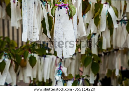 Tree of desires with suspended notes close-up as background. - stock photo