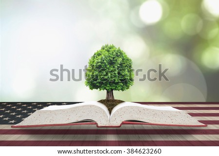 Tree of knowledge/ life growing from big archive open textbook on vintage USA flag pattern on old aged wood table, blur natural green background: Read across america day night concept: US CSR bio idea
