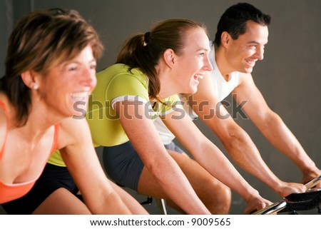 Tree people in a gym or fitness club; focus on girl in the middle