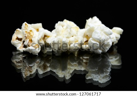 Tree pieces of popcorn isolated in a black background with reflection