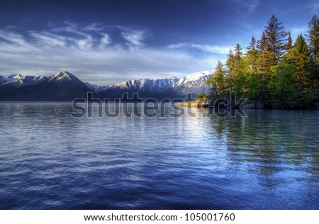 Tree reflections in the water of the Turnagain Arm of the Cook Inlet near Hope Alaska in soft evening light with blue skies.