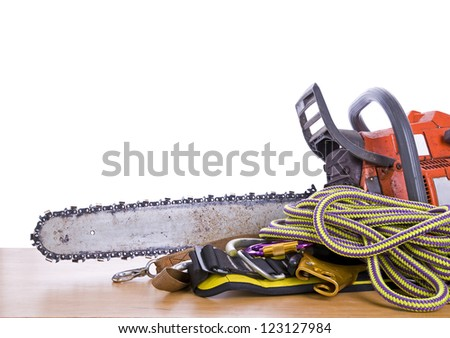 tree surgeon tools on desk including chainsaw, harness and rope - stock photo