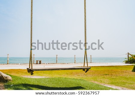 Tree swing in a garden with ocean background