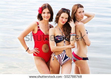 Tree young lovely women having a rest on the beach - stock photo