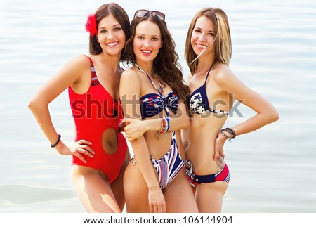 Tree young lovely women having fun on the beach - stock photo