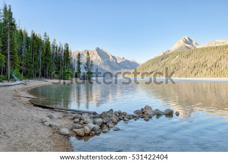 Trees and a mountain vista reflecting in the waters of Beautiful Redfish Lake in central Idaho.