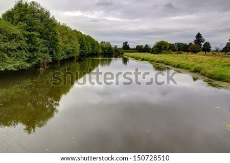 trees and meadows along a river  - stock photo