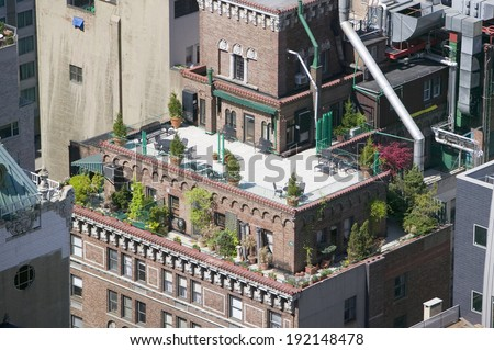 Trees and plants grow on outdoor deck of New York City apartment building in Manhattan, New York - stock photo