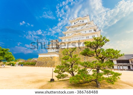 Trees in foreground of inside keep courtyard at base retaining wall on grounds of Himeji-jo castle on a clear sunny day in Himeji, Japan after early 2015 renovations. Horizontal - stock photo
