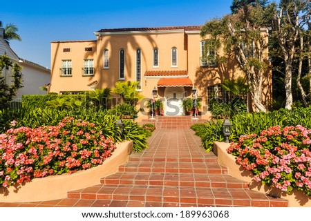 Trees next to a two story house with sloping entryway - stock photo
