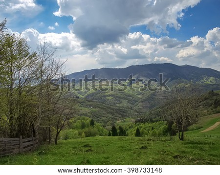 Trees next to a wooden fence on a background of mountains - May mountain landscape Karpaty, Ukraine. 