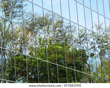 Trees reflected in windows of modern office building - stock photo
