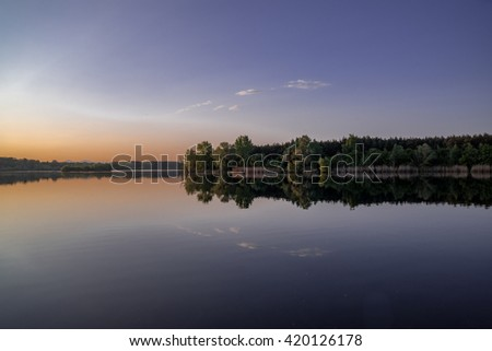 trees reflecting in the water with sunset and dark blue and purple colors