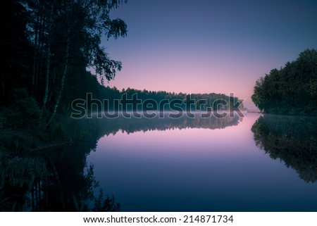 Trees reflecting in water smooth surface at early morning sunrise - stock photo