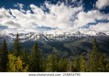 Trees, snow covered mountains and blue sky in Rocky Mountain National Park in Colorado - stock photo