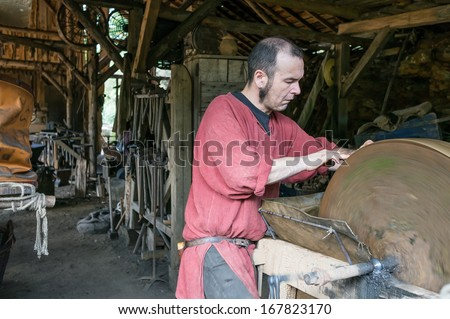TREIGNY, FRANCE - OCTOBER 21: Worker in medieval costume grind a knife on October 21, 2013 in Treigny, France. Guedelon Castle is a medieval construction project that will be completed in the 2020s.