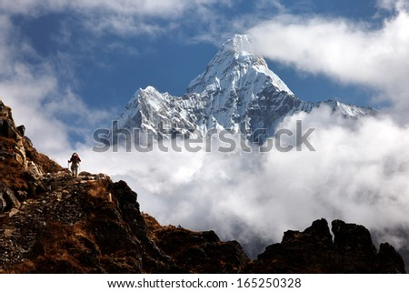 Trekker below Ama Dablam in the Nepal Himalaya - stock photo
