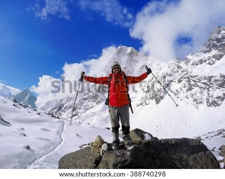 Trekker winner on the top, Himalaya mountains, man trekker after trek to Everest Base camp, active sport in mountains, mountaineer in snowy mountains, red jacket mountain climber near Everest, Nepal - stock photo