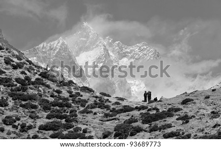 Trekkers in the Himalayas standing against peak Lhotse (8516 m) (black and white) - Nepal, Himalayas