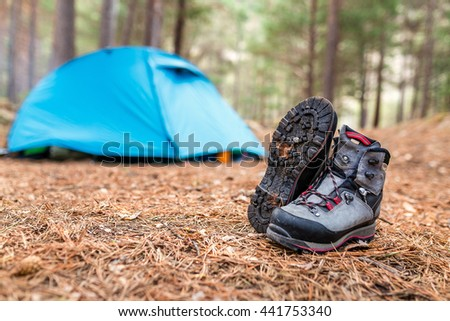 Trekking hiking boots on background with blue tourist tent camp in the wild forest - stock photo