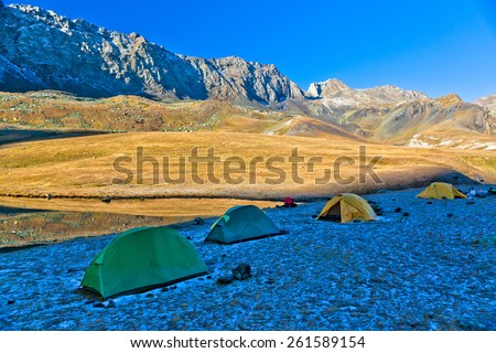 Trekking tourists camp in the mountains in the morning. Picture was taken during the hike in scenic Caucasus mountains at autumn, Arhiz region, Abishira-Ahuba range, Karachay-Cherkessia, Russia - stock photo