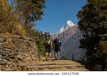 Trekking with Machhapuchchhre mountain in background - Fish Tail in English is a mountain in the Annapurna Himalya, Nepal - stock photo