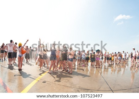 TRENCIN,SLOVAKIA - JULY 7:Firetruck sprays water on visitors of Bazant Pohoda Music Festival at the Trencin Airport in Trencin, Slovakia on July 7, 2012.