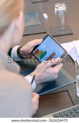 Trend of stable growth. Female and male business partners look at a screen of the tablet device where they see diagram in selective focus