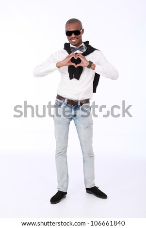 Trendy African business man smiling with sunglasses,a silver bow tie, jeans,white long shirt  and a black jersey on, with his hands in the shape of a heart close to his chest. on a white background - stock photo