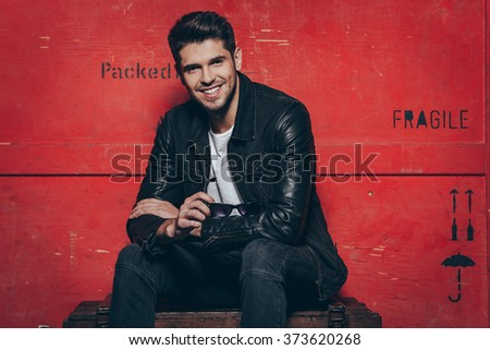 Trendy and charming. Handsome cheerful young man holding his sunglasses and looking at camera with smile while sitting on wooden chest against red background - stock photo