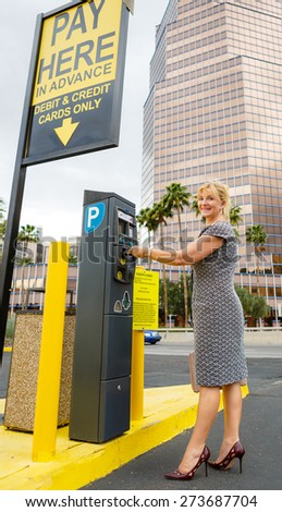 Trendy attractive senior aged business woman 55-65 years with a lovely charming smile paying for parking in the street. Positive human emotion, facial expression - stock photo