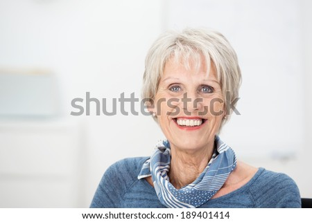 Trendy attractive senior woman with a lovely charming smile wearing a stylish scarf, head and shoulders portrait with copyspace