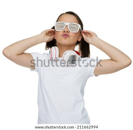 Trendy attractive young girl in white shutter shades standing proudly with her head tilted back and a set of headphones for her music around her neck, isolated on white - stock photo