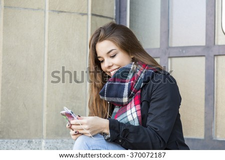 Trendy attractive young girl listening to music on her mobile phone and earplugs sitting on urban steps checking the tunes in her library