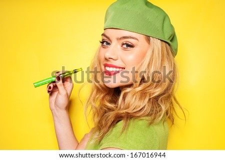 Trendy beautiful blond woman in a stylish green ensemble with an e-cigarette in her hand turning to smile at the camera, over yellow - stock photo