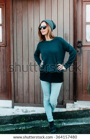 Trendy beautiful cool hipster blond girl wearing a gray hat and glasses against a wood wall. Street fashion concept, Urban style. - stock photo